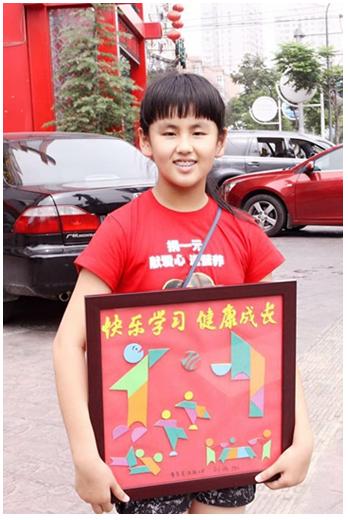 """2011年,刘雨泓是富源路小学五年级的一名小学生和同学一起参加了""""捐一元""""项目的换物之旅。在经历多次失败后,她通过自己的七巧板拼图作品,以物换物交换了帆船模型、自行车、平板电脑...最终换到了一件价值6900元的哈雷皮衣,最后在义卖活动中和其他小伙伴们一起筹集善款近万元,为云南山区的孩子换来了鸡蛋牛奶的营养加餐。"""